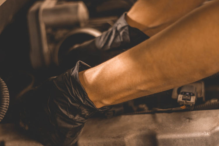 Woman Mechanic changing spark plugs under the hood of an SUV in the shop. Arms Automobile Engine Compartment Forearms Hands Machine Mechanic Mechanical SUV Woman Working Auto Car Close-up Engineering Fingers Gloves One Person Skin Under The Hood Wrists