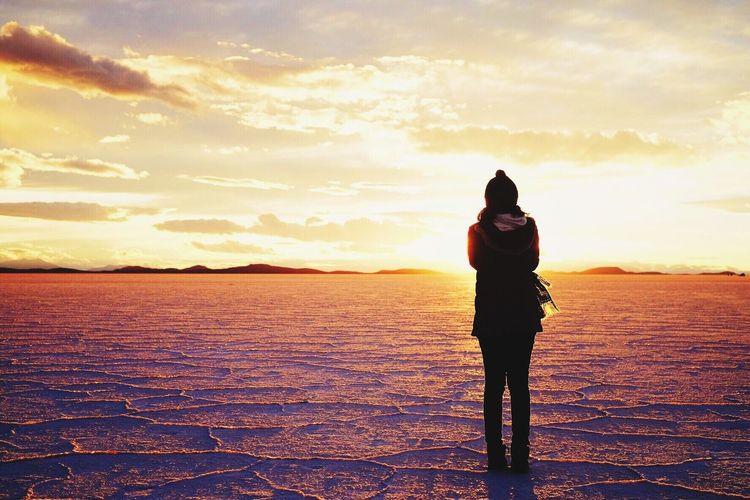 Full length of woman standing on landscape against sky during sunset
