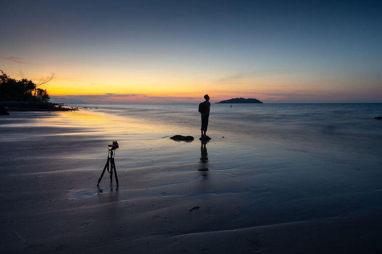 Camera on tripod with silhouette man standing at beach against sky during sunset
