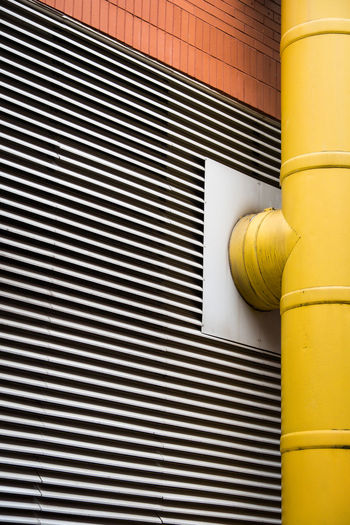 Close-up of yellow metal against wall