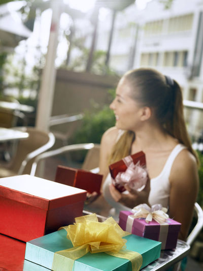 Smiling Woman Sitting By Gifts In Restaurant