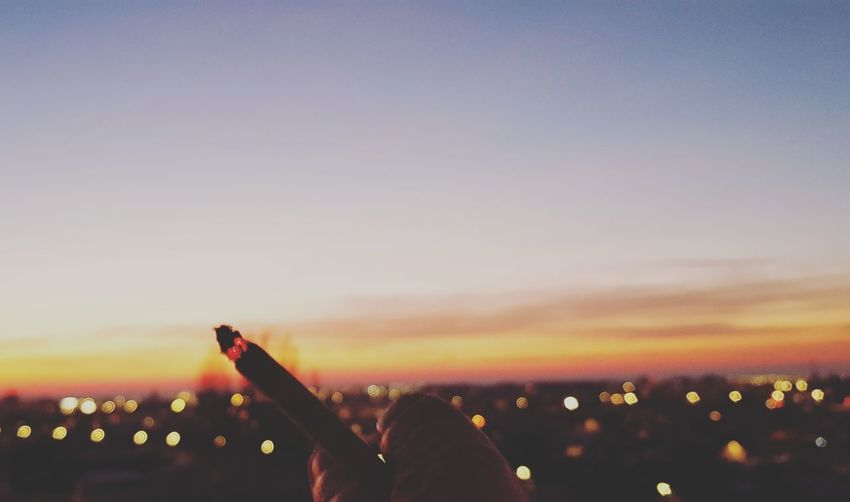 Cropped hand holding illuminated cigarette against city during sunset