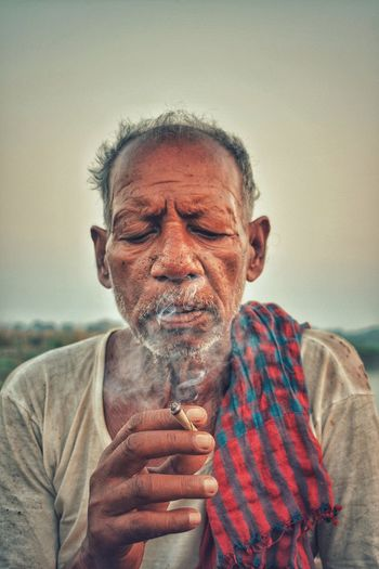 Close-up of mature man smoking beedi against clear sky