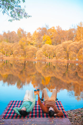 People sitting by lake during autumn