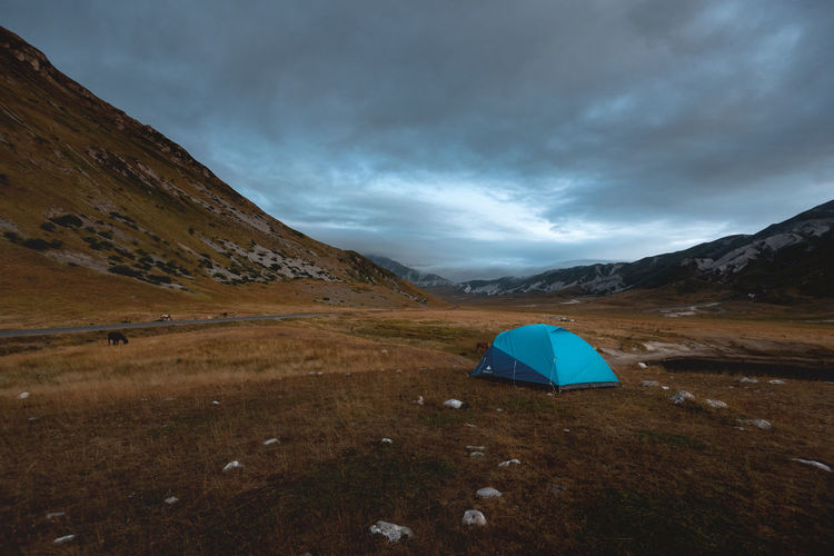 Tent on field by mountain against sky