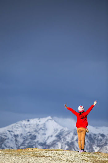 Full Length Of Woman Standing With Arms Raised On Mountain Against Sky