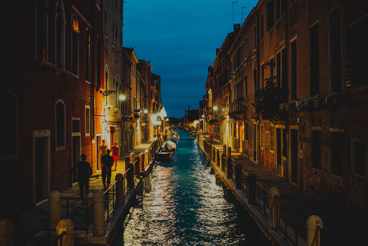 A canal in venice italy amidst buildings in city at night