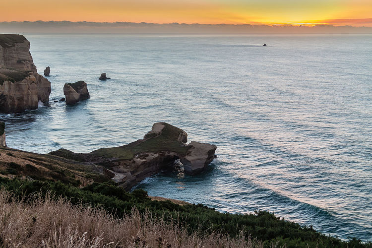 Tunnel Beach is a locality 7.5 kilometres (4.7 mi) southwest of the city centre of Dunedin, New Zealand. Located just south of St Clair, Tunnel Beach has sea-carved sandstone cliffs, rock arches and caves. https://en.wikipedia.org/wiki/Tunnel_Beach Tunnel Beach Dunedin New Zealand Beauty In Nature Dawn Rock Formation Sea Sky Water Wave