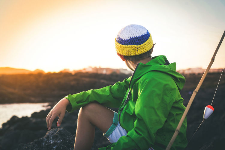 Boy sitting by fishing rod on rock against sky during sunset
