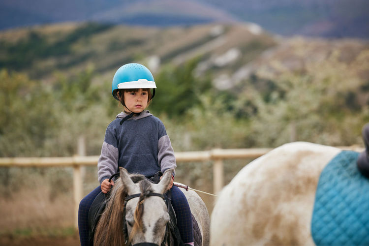 5 year old girl riding a horse with lovely expression
