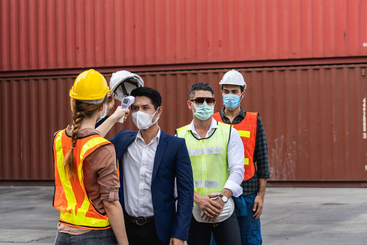 Rear view of worker checking temperature at commercial dock
