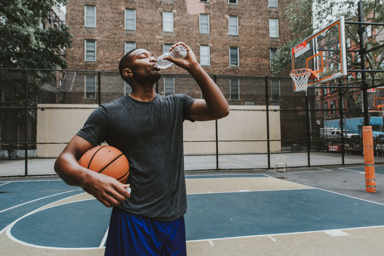 Male athlete holding basketball while drinking water in court