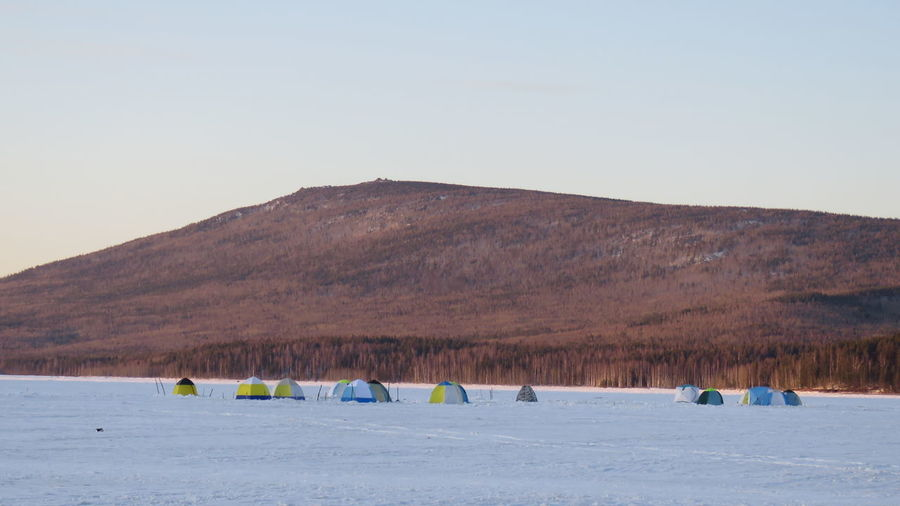 Tents on snow covered landscape against mountain during sunset
