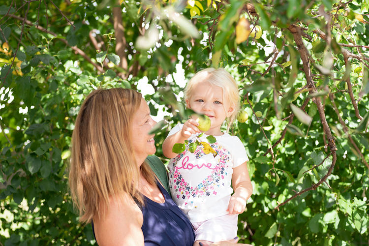 Mother and daughter against plants
