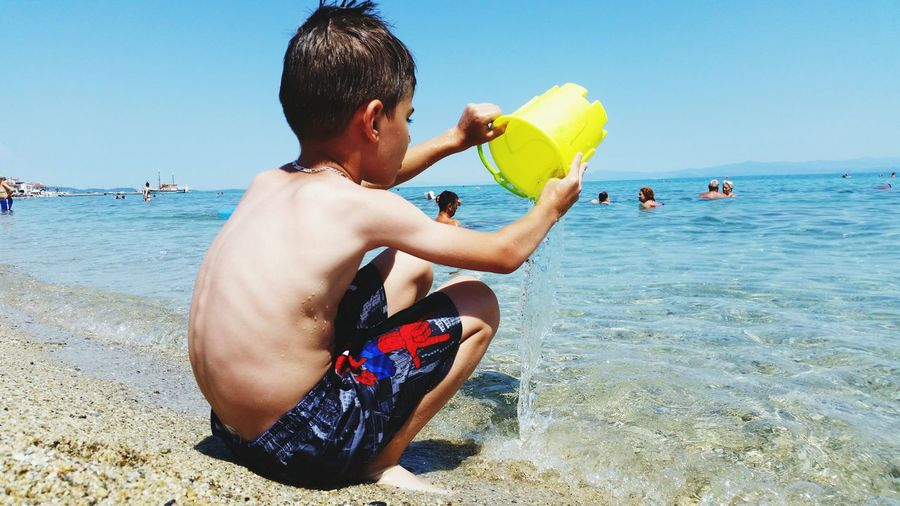 Side view of boy playing with water while crouching at beach against clear blue sky during sunny day