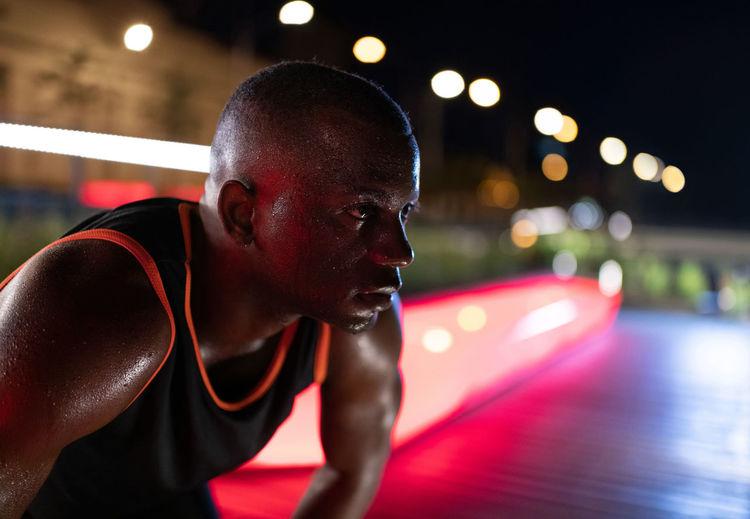 Young man looking at illuminated camera at night