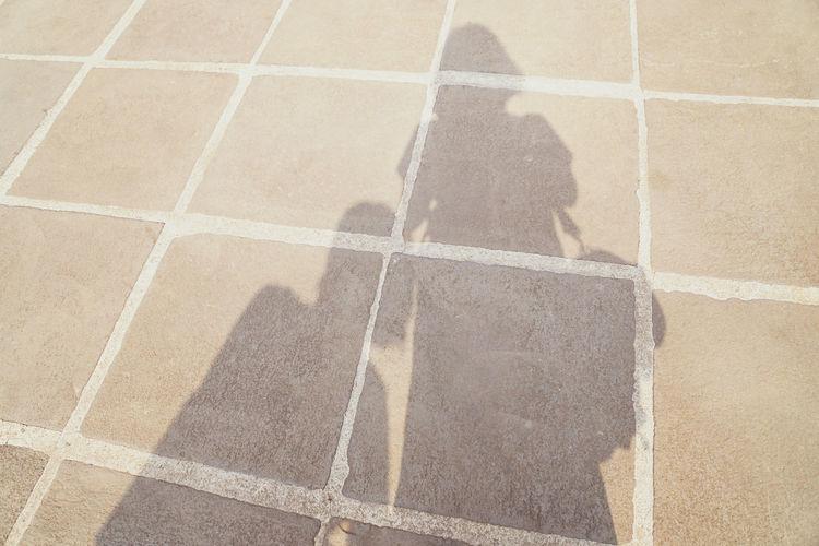 High angle view of shadow on tiled floor