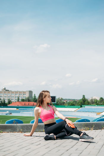 Woman sitting in swimming pool against sky