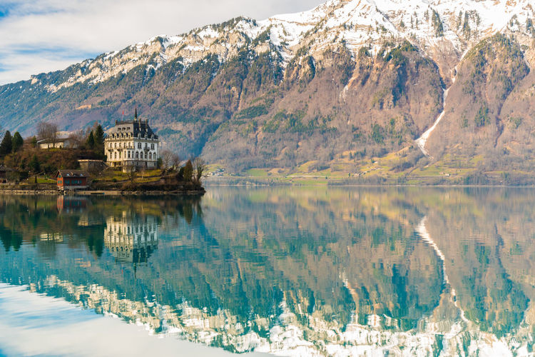 Reflection of building in lake against snowcapped mountains