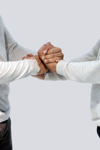 Midsection of couple holding hands over white background
