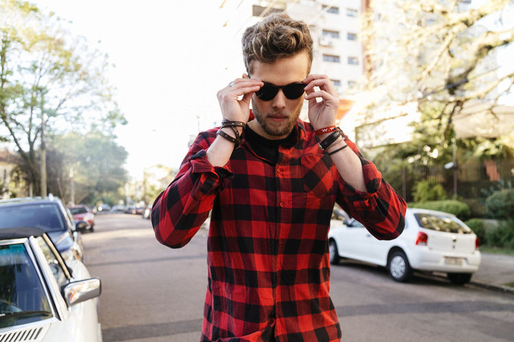 Adult Adults Only Car Casual Clothing Day Land Vehicle Lifestyles Mode Of Transport One Person One Young Man Only Outdoors People Real People Road Standing Transportation Wireless Technology Young Adult Young Men