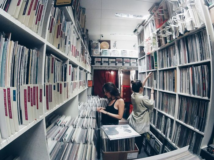 High Angle View Of Women Choosing Music Record At Store