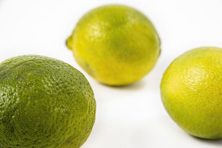 Close-up of green fruits against white background
