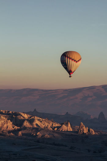 Hot air balloon flying over rocks against sky
