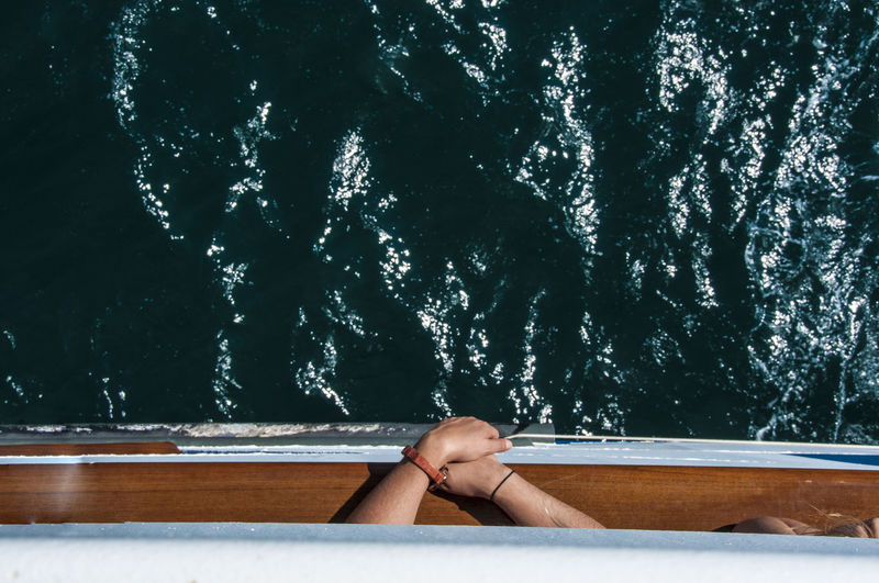 Cropped Image Of People In Boat On Sea