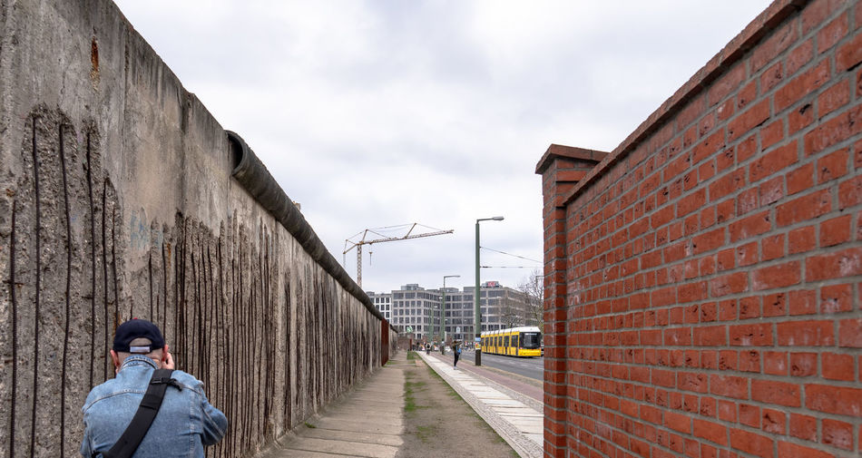 Rear view of man standing by wall against sky