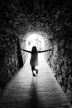 Arched Archway Black & White Brick Wall Light At The End Of Tunnel Passage Person Shadows & Lights Tunnel