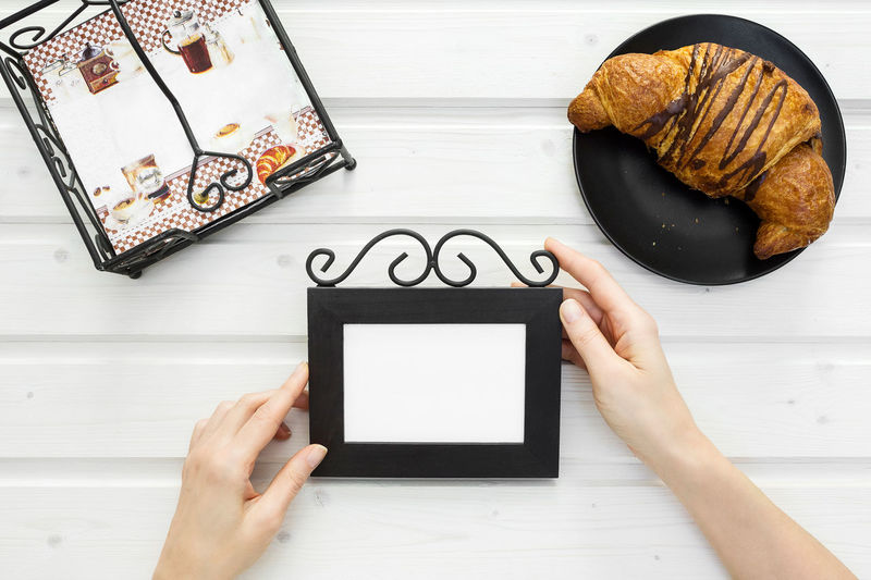 Morning tabletop scene with female hands holding a blank frame on a white table Breakfast Croatia Morning White Frame Blank Frame Croasant Decoration Directly Above Female Hands Female Hands Holding Flat Lay Food And Drink Frame Hand High Angle View Holding Human Hand Mock Up Stationary Table Tabletop Tabletop Scene View From Above Wedding Card White Table
