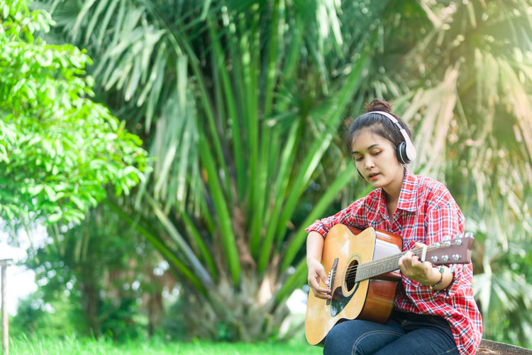 Acoustic Guitar Adult Artist Casual Clothing Day Garden Guitar Headphone Holding Leisure Activity Model Asian Music Musical Instrument Musician Nature One Person Outdoors Plant Playing Plucking An Instrument Sitting Smiling String Instrument Tree Young Adult