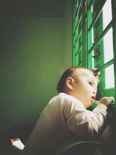 Baby boy looking though window at home