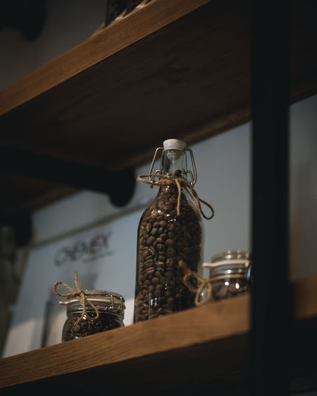 Coffee Beans in Glass Bottles in Coffee Shop Indoors  No People Container Wood - Material Still Life Bottle Low Angle View Shelf Glass - Material Home Interior Table Selective Focus Focus On Foreground Food And Drink Antique Arrangement Architecture Close-up Wall - Building Feature Silver Colored Ijas Muhammed Photography
