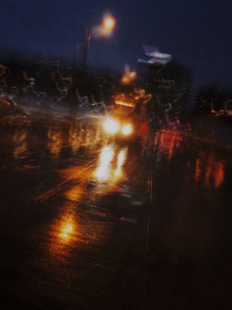 ILLUMINATED LIGHT TRAILS ON STREET DURING RAINY SEASON