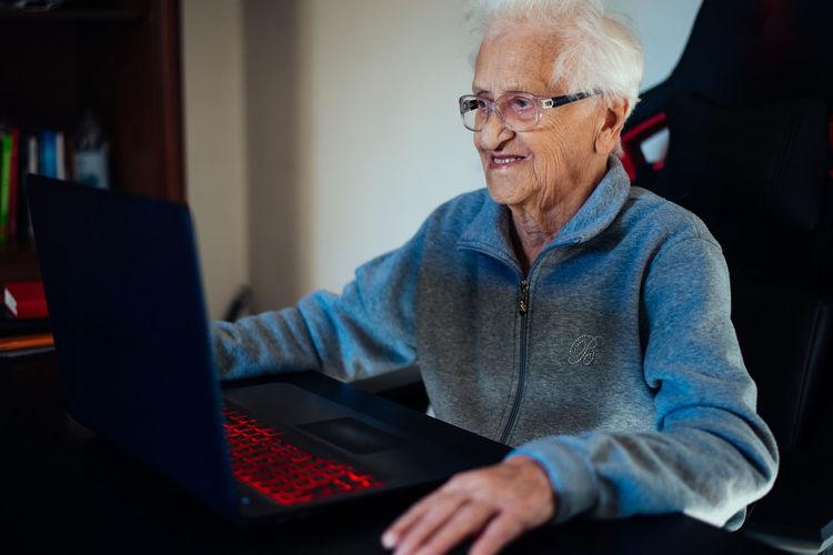 Smiling senior woman using laptop while sitting at home