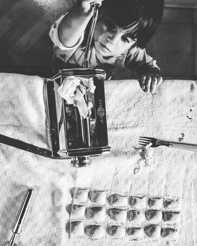 High angle view of boy holding pasta maker by ravioli on table