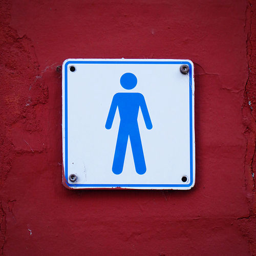 Male toiletsign on old wall