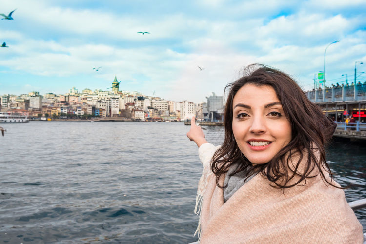 Portrait of smiling woman in city against sky