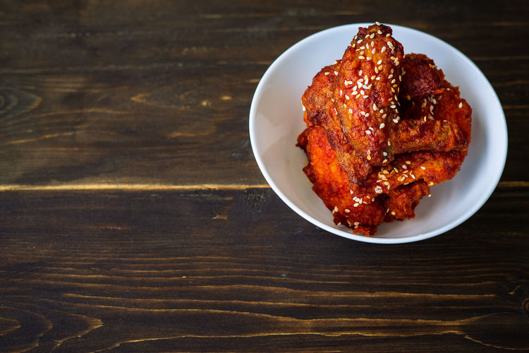 Fried chicken in a spicy sauce and sesame seeds. food korean cuisine on a wooden background.