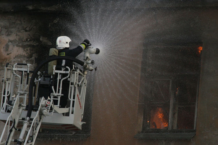 Rear view of firefighter on crane extinguishing fire in building