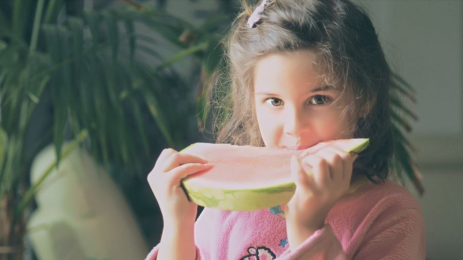 Close-Up Portrait Of Girl Eating Watermelon Slice At Yard On Sunny Day