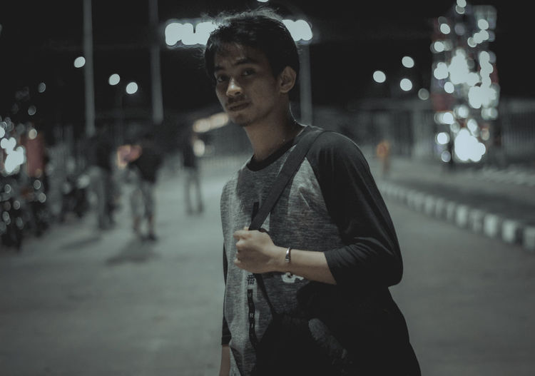 Young man looking away in city at night