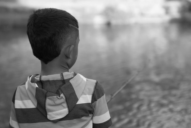 The fish tale was bigger than he was Boys Casual Clothing Child Childhood Contemplation Day Fishing Focus On Foreground Innocence Leisure Activity Lifestyles Looking Males  Men Nature One Person Park Portrait Real People Standing Waist Up Water