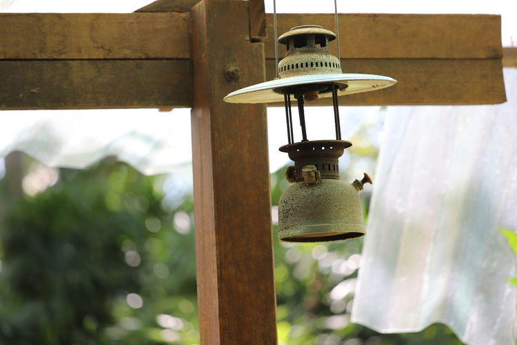 Close-up of lamp hanging on wooden post