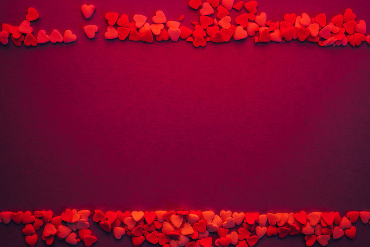 Close-up of heart shape candies on red background