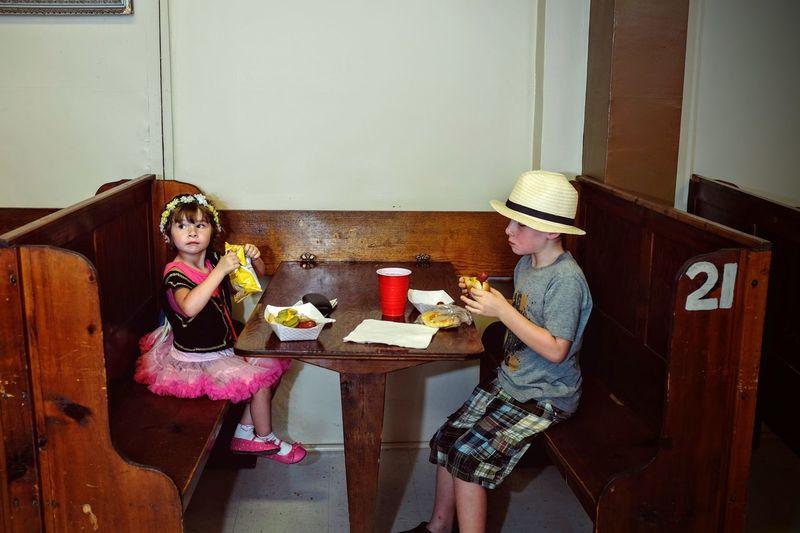 Siblings eating food at table