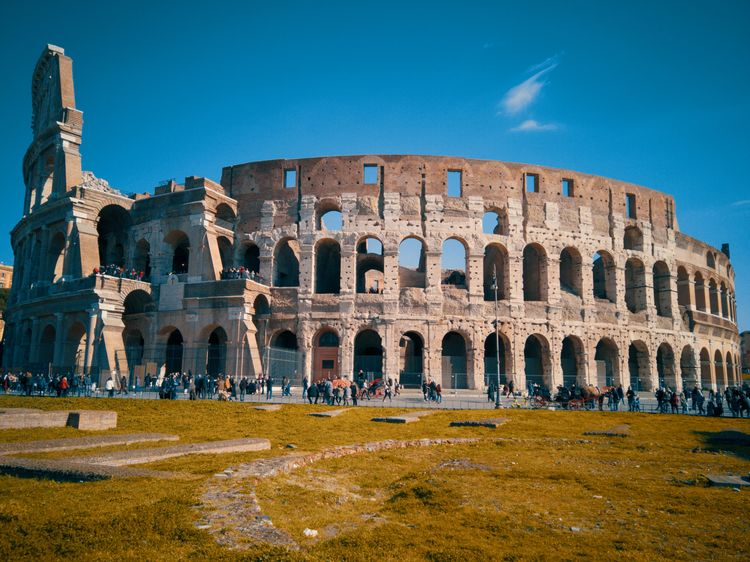 The Colloseum in Rome Tourism Tourist Attraction  Journey Stone City Ancient Civilization Old Ruin Ancient Business Finance And Industry Arts Culture And Entertainment Blue Arch Sky Amphitheater Roma Roman Arched Ancient Rome Visiting Historic Lazio Archaeology Monument Ancient History The Past Civilization