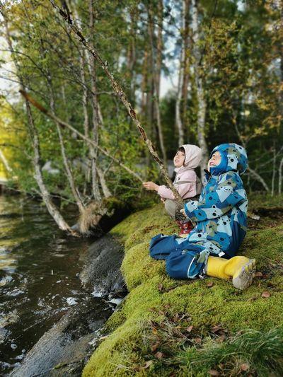 Full length of boys fishing in river against trees